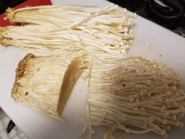 Cut the ends of the enoki mushrooms off