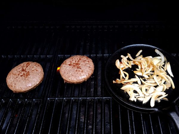 2 Burger Patties on the Grill with Caramelized Onions