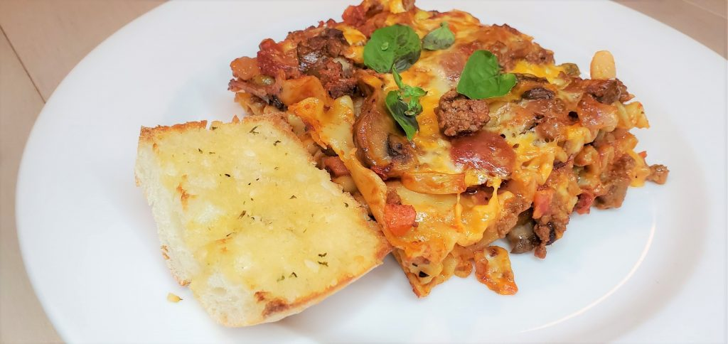 Lasagna topped with basil served with garlic bread